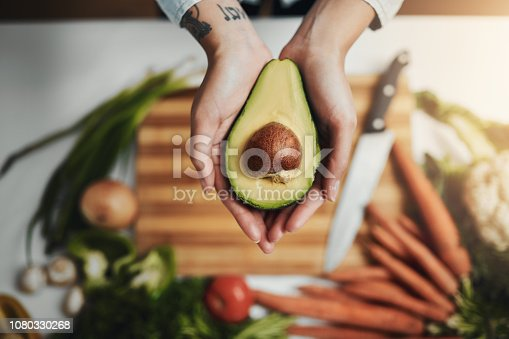 Cropped shot of a woman holding an avocado slice while preparing a healthy meal at home
