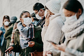 Shot of a young man and woman wearing masks while travelling in a foreign city