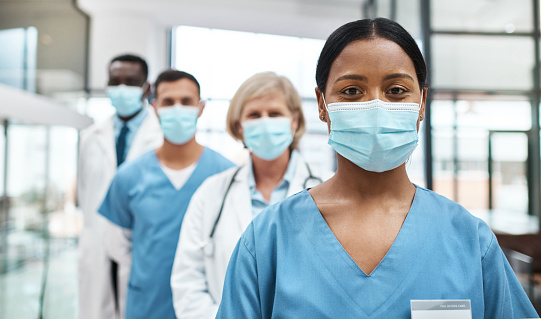 Portrait of a group of medical practitioners wearing face masks while standing together in a hospital