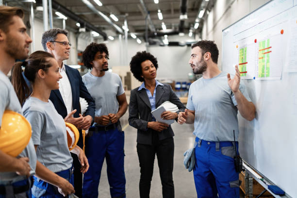 As you can see, we follow this working plan here! Young manual worker presenting new business strategy to company managers and his colleagues in a factory. staff meeting stock pictures, royalty-free photos & images