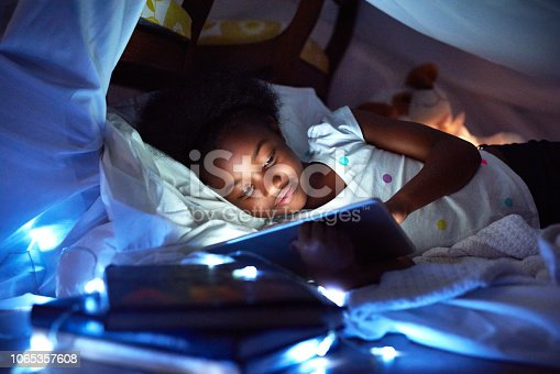 Cropped shot of an adorable little girl using a digital tablet while lying in bed