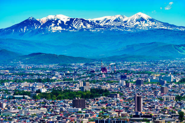 asahikawa city, summer cityscape and daisetuzan mountain range. hokkaido, japan - sapporo stock photos and pictures
