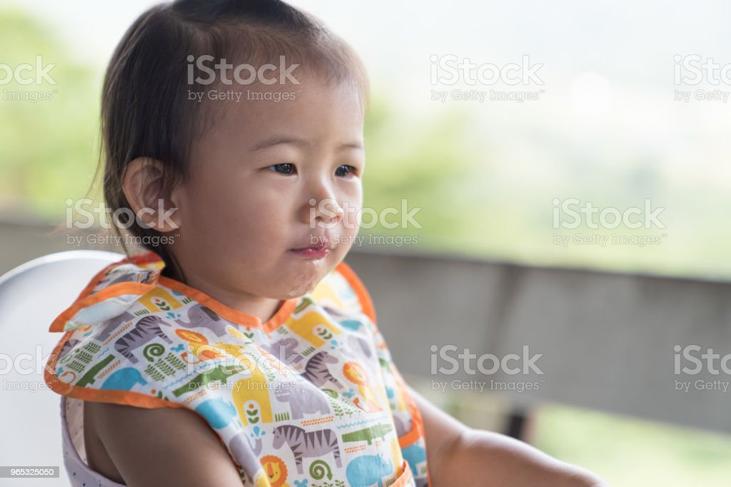 Asain cute baby girl eatting ice water on white chair. royalty-free stock photo