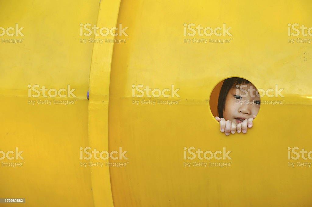 asain girl peeks through hole in playground royalty-free stock photo