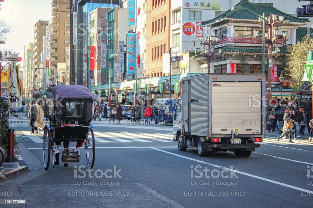 There are a rickshaw and a modern lorry driving on the road