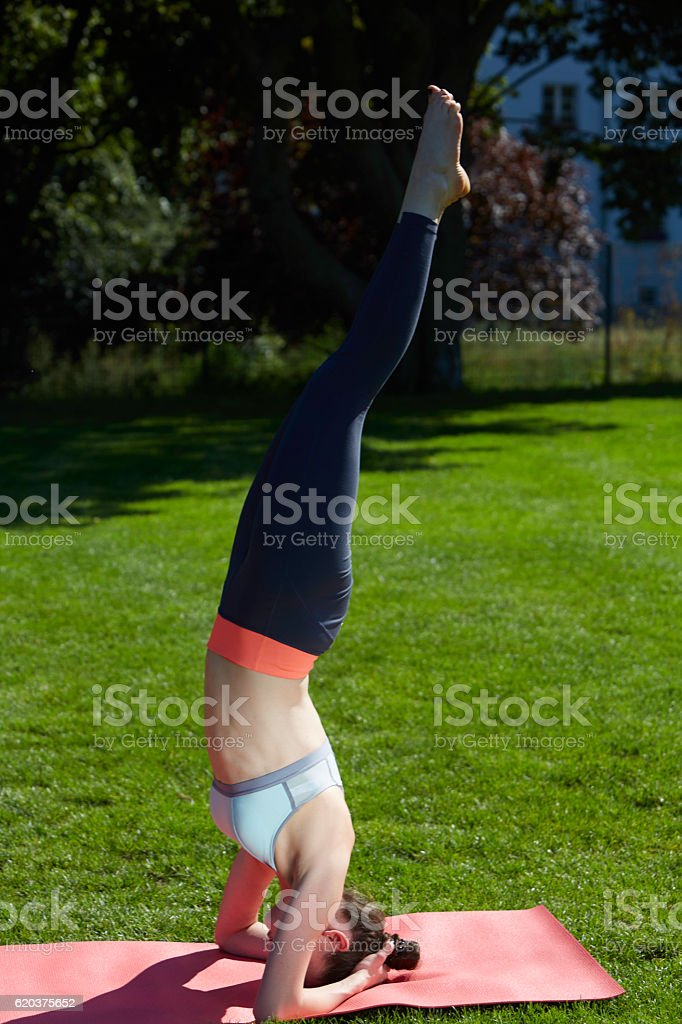 Asana yoga in park: supported headstand on grass foto de stock royalty-free