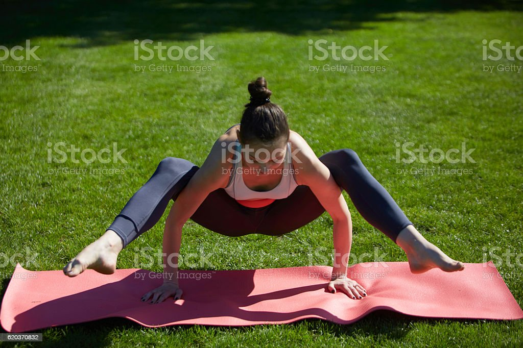 Asana yoga on wrists in park: peacock pose with variation foto de stock royalty-free