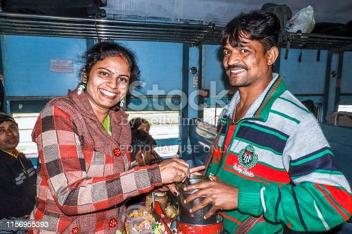 Asansol, West Bengal, India - January 24, 2017;  a hawker selling jhalmuri  (a popular snack in West Bengal) with smiling face in the train. near Asansol of India.