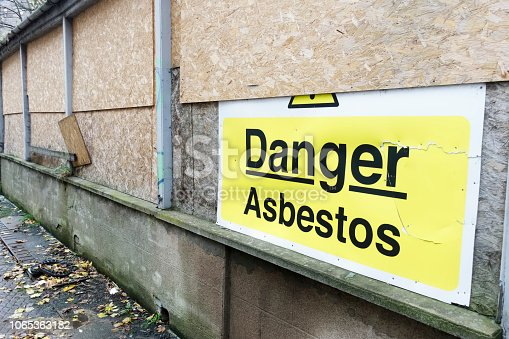 Asbestos danger sign at building construction site refurbishment of old building uk