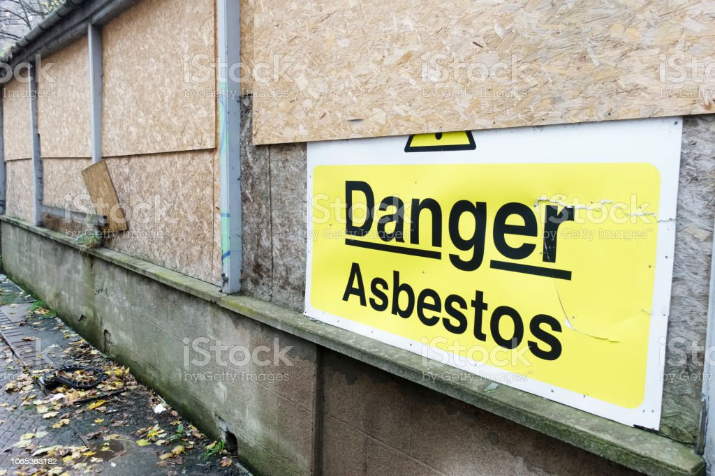 Asbestos danger sign at building construction site refurbishment of old building stock photo