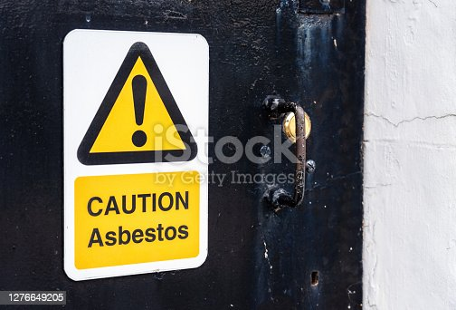 A sign on the entrance door to an old building, warning people of the health and safety dangers of asbestos being present.
