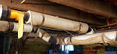 Basement plumbing pipes wrapped with asbestos insulation.