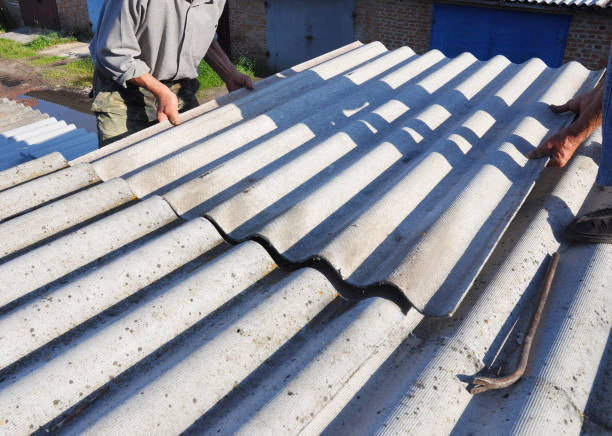 Asbestos Removal. House asbestos roof repair with roofer hands. Roofers Roofing Construction and Roof Repair. stock photo