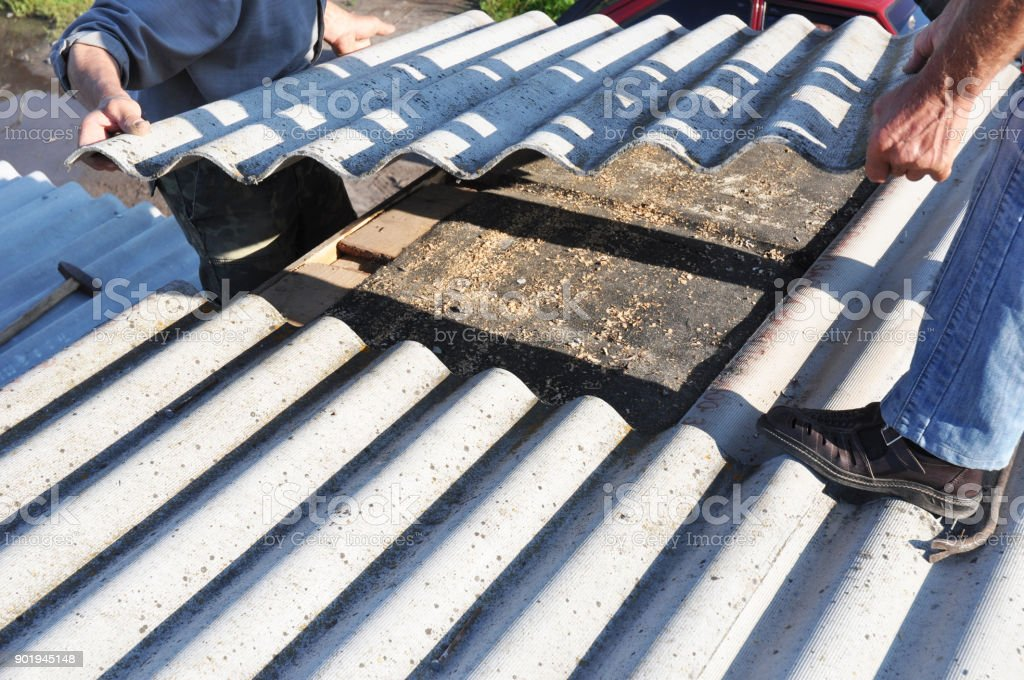 Asbestos workers repair asbestos roof. Asbestos removal. stock photo