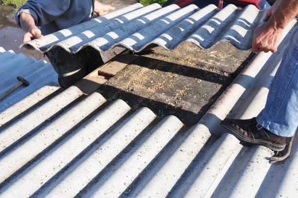Asbestos workers repair asbestos roof. Asbestos removal. - foto stock