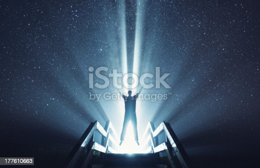 A man is lifted into the stars.  Composite image.
