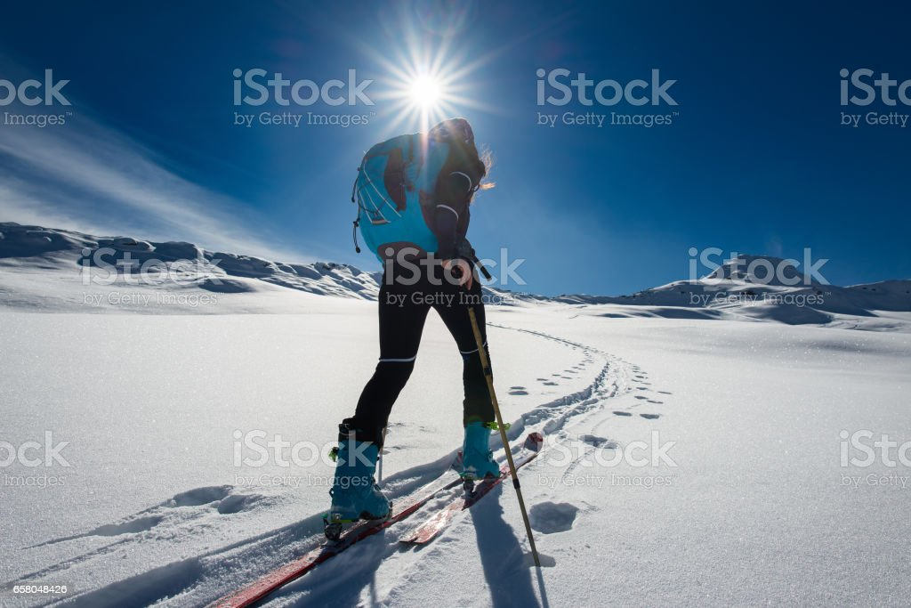 Ascent with ski mountaineering and climbing skins for a single woman stock photo