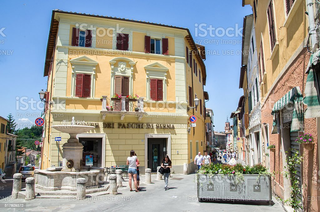 Asciano, Italy - People walk in the small square stock photo