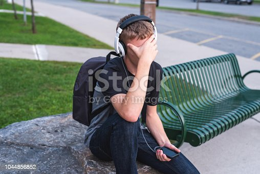 811258918 istock photo Ashamed teenager sitting on a rock outside of a school while listening to music. 1044856852