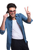 Happy young fashion man showing the victory sign while talking on the phone, isolated.