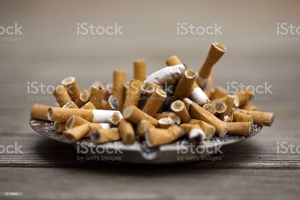 Ashtray bulging with cigarettes stock photo