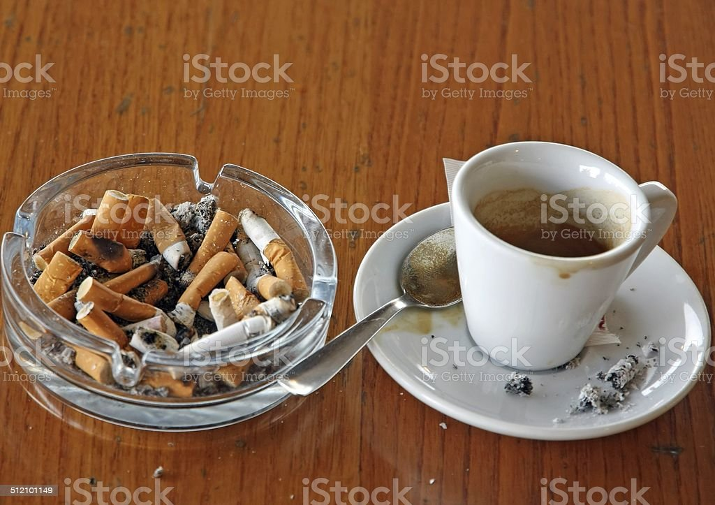 ashtray chock full of cigarette butts stock photo