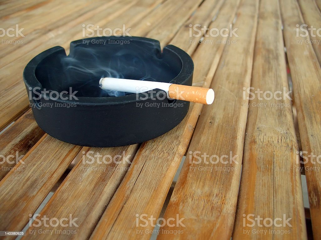 Ashtray with lit cigarette stock photo