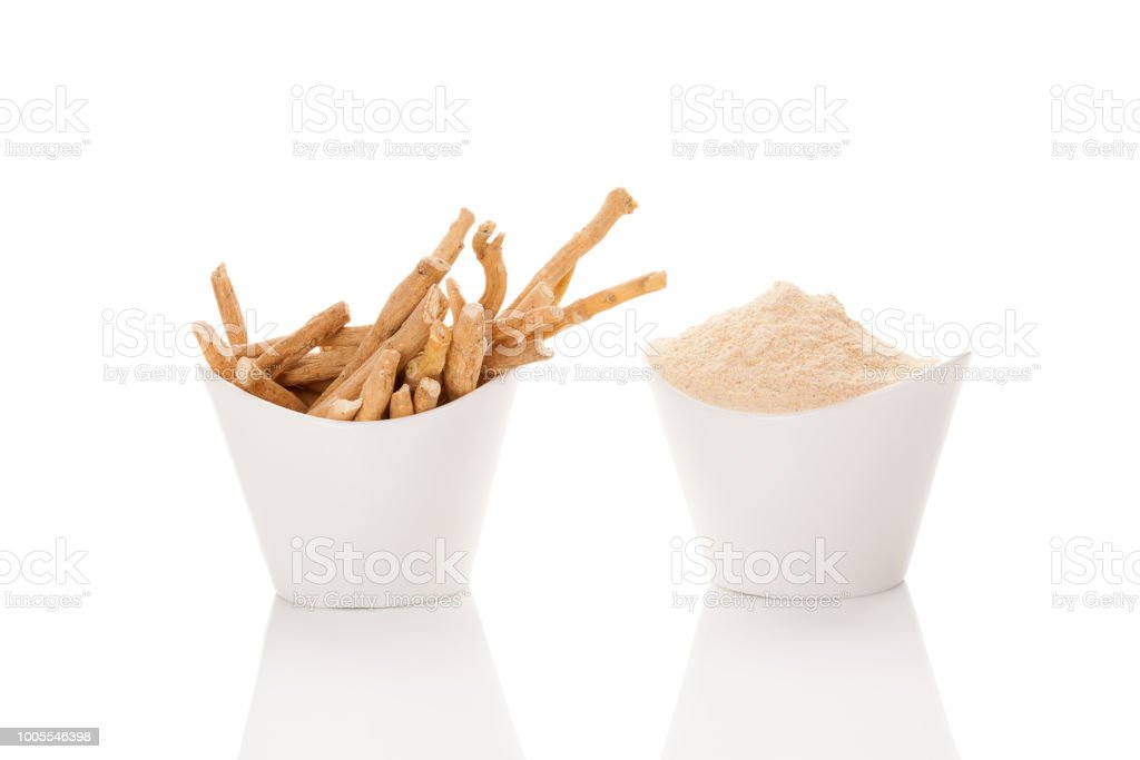 Ashwagandha powder and roots in white cups. stock photo