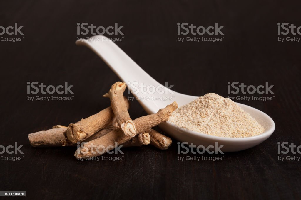 Ashwagandha root and powder in white spoon on dark background. stock photo