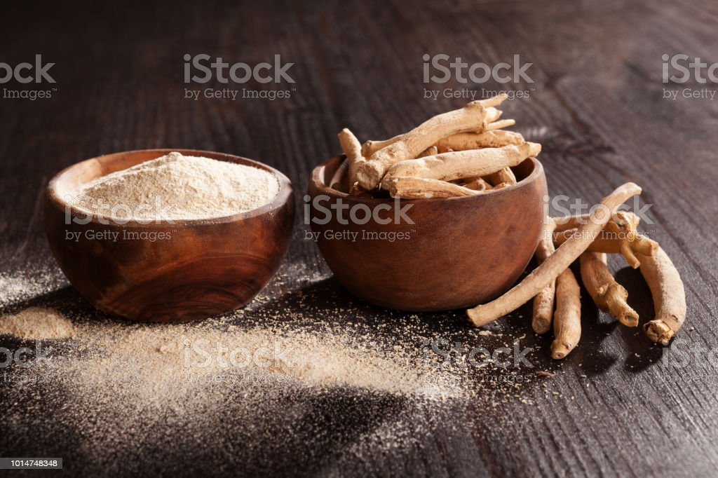 Ashwagandha root and powder in wooden cups on dark background. stock photo