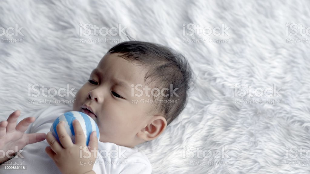 e98b1e15c9e1 7 meses de idade um bonito menino Ásia sorria deitado sobre um cobertor.  foto royalty