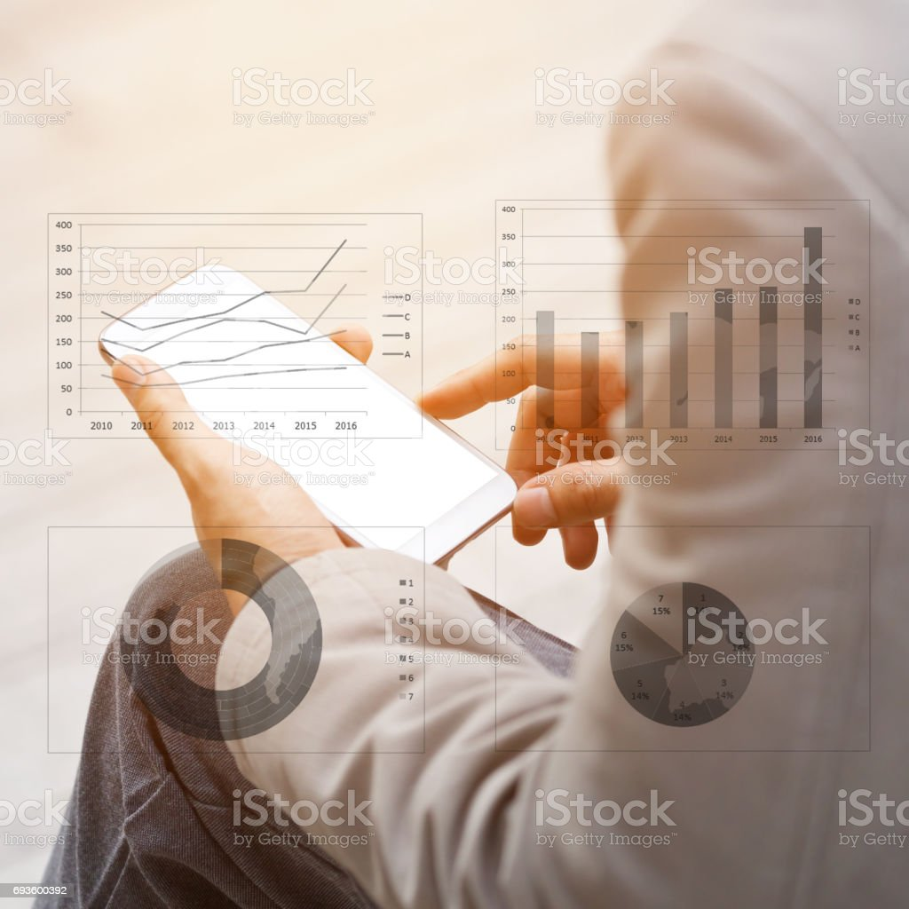 Asia business man hand touch screen on smartphone and business graph background. stock photo