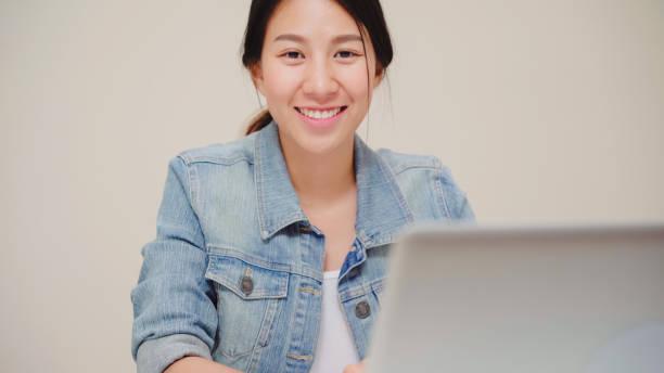 Asia Geschäftsfrau gefühl glücklich lächelnd und Blick in die Kamera, während entspannen im Home-Office. Junge asiatische Frau arbeiten mit Laptop auf dem Schreibtisch im Wohnzimmer zu Hause. – Foto