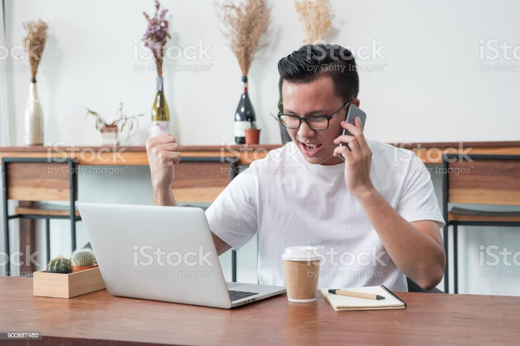 asia casual man arm up celebrate good new from mobile at laptop in coffee shop,success business concept,work outside office,work at home. stock photo