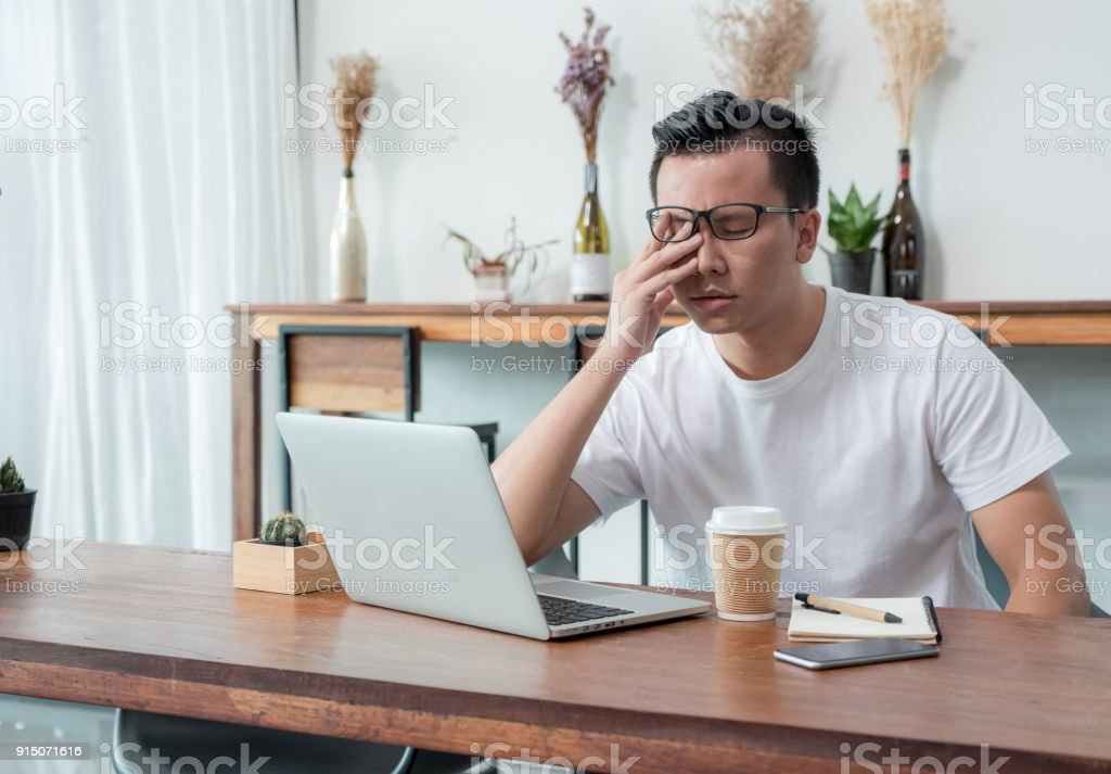 asia casual man cover face with hand upset from work in front of laptop computer in coffee shop,stress emotion concept,work outside office,work at home. stock photo