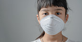 Asia child who have to wear a dust safety mask, Because the air is polluted and may cause her illness