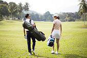 Asia Chinese couple walking together in the golf course with their golf bags.
