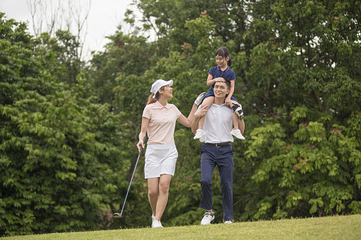 Asia Chinese family golfer having fun and bonding with daughter on the golf course