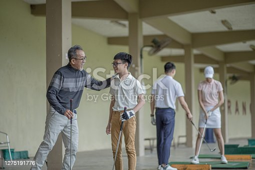 istock Asia Chinese grandfather guide grandson golf lesson at driving range during rainy day. Grandson hit a success shot and give high five celebrating. 1275191776