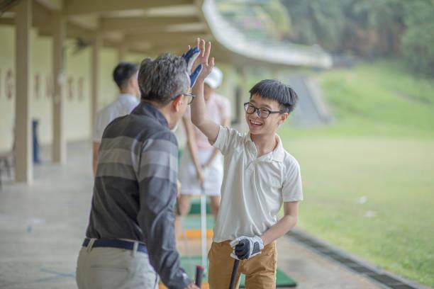 châu á ông nội trung quốc hướng dẫn cháu trai bài học golf tại phạm vi lái xe trong ngày mưa. cháu trai đã bắn thành công và cho cao năm ăn mừng. - concentration hình ảnh sẵn có, bức ảnh & hình ảnh trả phí bản quyền một lần
