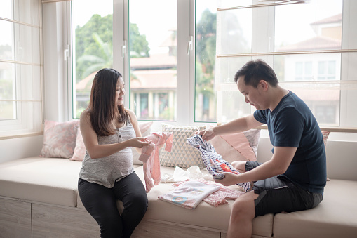 asia chinese pregnant woman getting ready for her new born baby preparing baby cloth and baby room with her husband