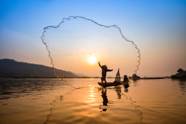 Asia fisherman net using on wooden boat casting net sunset or sunrise in the Mekong river Asia fisherman net using on wooden boat casting net sunset or sunrise in the Mekong river / Silhouette fisherman boat with mountain background people life on countryside indochina stock pictures, royalty-free photos & images