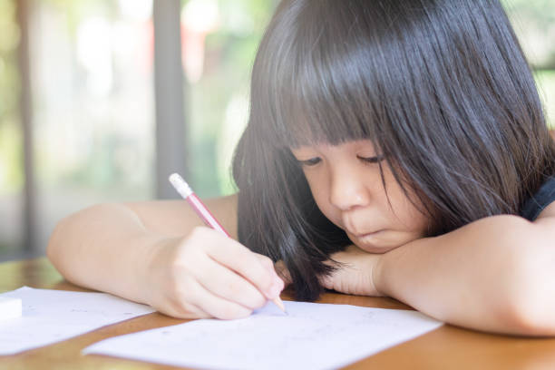 Asia kid girl doing boring homework with bored feeling at home. Female cute child concentrate write on paper. Asian students practice math subject for test. Student study at house Asia kid girl doing boring homework with bored feeling at home. Female cute child concentrate write on paper. Asian students practice math subject for test. Student study at house learning difficulty stock pictures, royalty-free photos & images