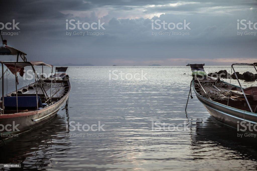 Asia levensstijl landschap traditionele Aziatische boten gericht op de horizon in kalme zee tijdens donkere humeurig zonsondergang - Royalty-free Avondschemering Stockfoto