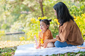 Asia little girl blowing a soap bubble in the park with a greenery background and sitting beside her mother. Happy carefree childhood. Family outdoors activity. Happiness and holiday concept.