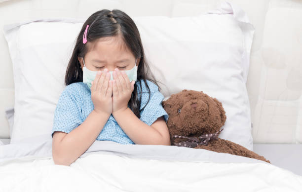 Asia little girl cough and waer hygienic mask. stock photo