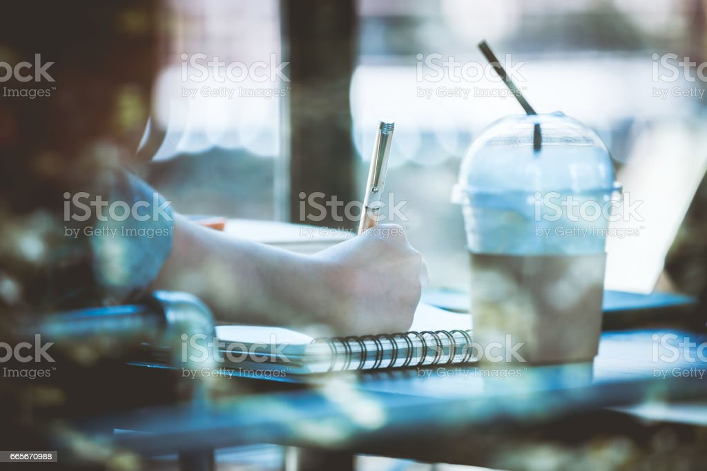 Asia teenage hipster in sitting alone at cafe with notebook stock photo
