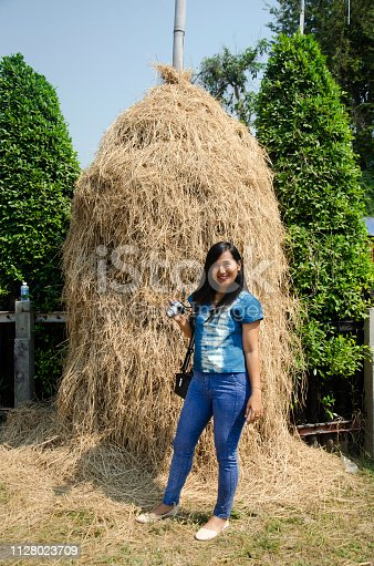 istock Asia thai woman travel visit and standing posing for take photo with straw stack 1128023709