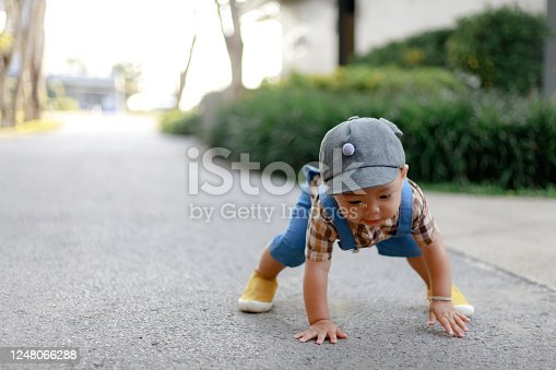 1 year old cute toddler Asia boy kid in bib jeans trying to stand up after fell with copy space.