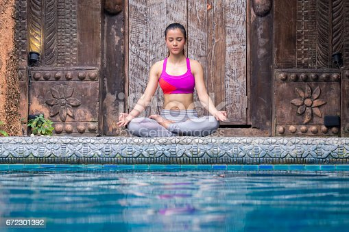 istock Asia woman doing yoga beside swimming pool 672301392